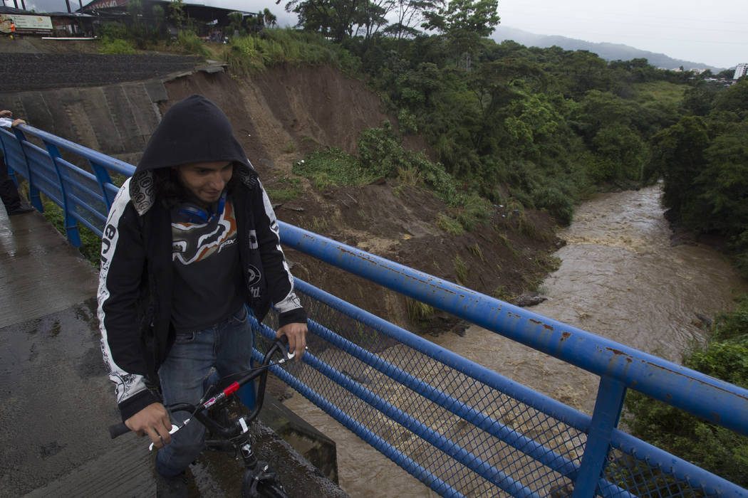 A cyclist rides over a bridge over the Maria Aguilar river on the outskirt San Jose, Costa Rica, Thursday, Oct. 5, 2017. Tropical Storm Nate formed off the coast of Nicaragua on Thursday and was b ...