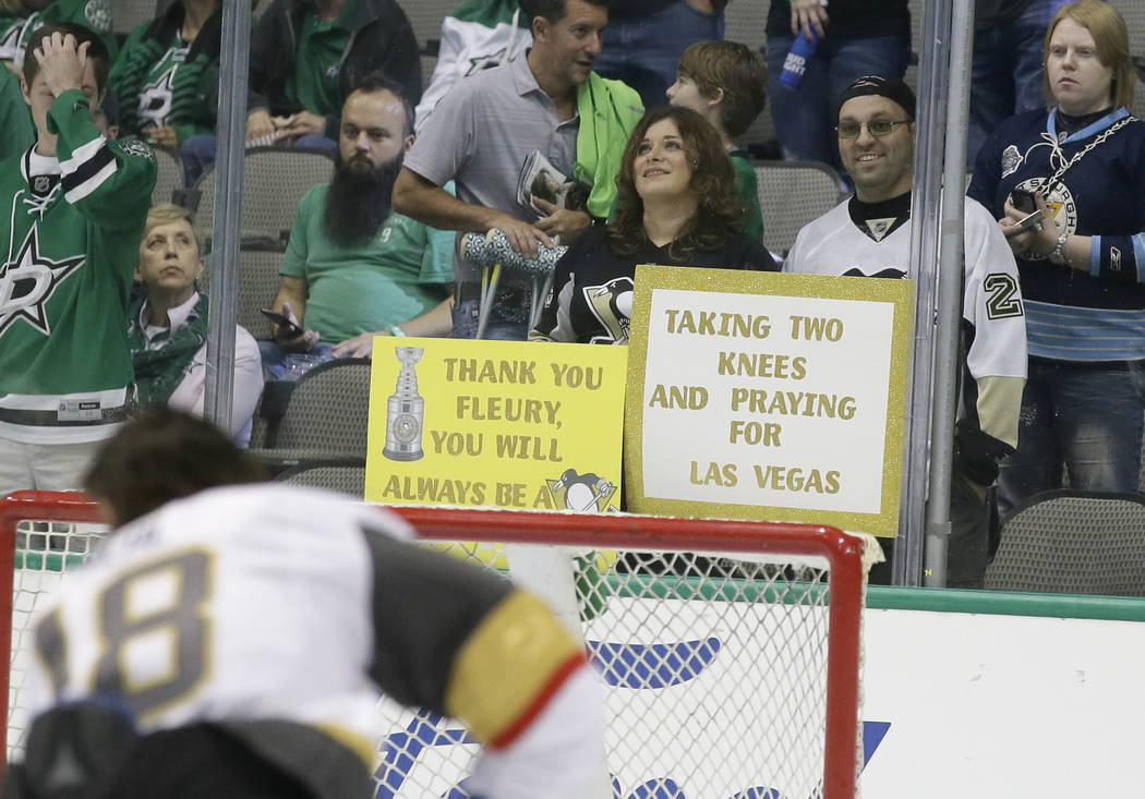 A fan holds a sign in the stands during warm ups before an NHL hockey game between the Vegas Golden Knights and Dallas Stars in Dallas, Friday, Oct. 6, 2017. (AP Photo/LM Otero)