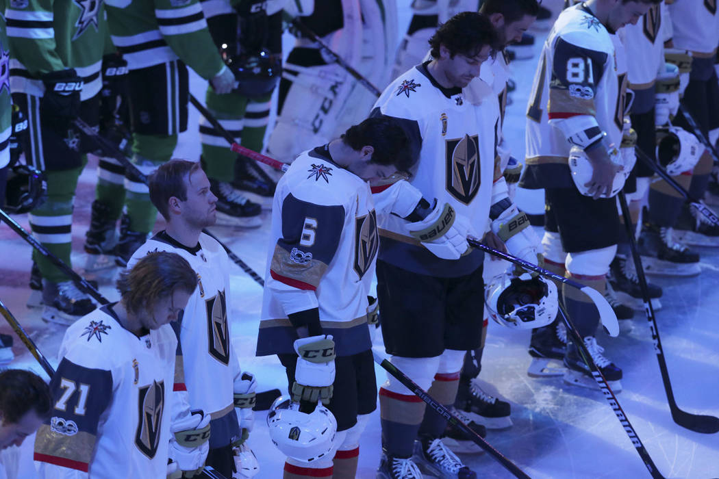 Vegas Golden Knights defenseman Colin Miller (6) bows his head as he lines up with teammates and the Dallas Stars for a moment of silence for shooting victims in Las Vegas before an NHL hockey gam ...