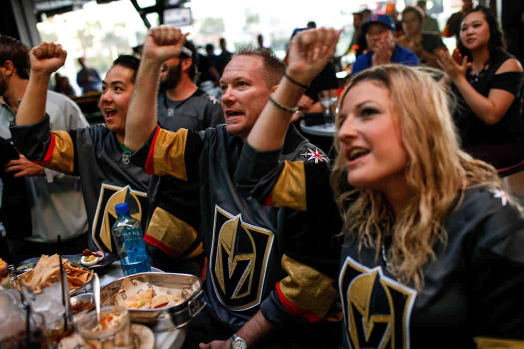 Michael Nguyen of Dallas, 32, left, Kirk MacDonald of Las Vegas, 41, center, and Stefanie MacDonald of Las Vegas, 26, right, cheer during a watch party for the Vegas Golden Knights season opener a ...