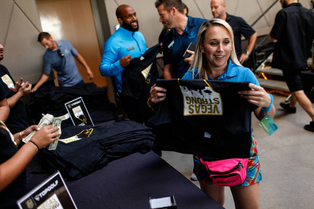 """Alyssa Rapovy of Las Vegas, 26, buys a """"Vegas Strong"""" t-shirt during a watch party for the Vegas Golden Knights season opener against the Dallas Stars at Topgolf in Las Vegas, Fr ..."""