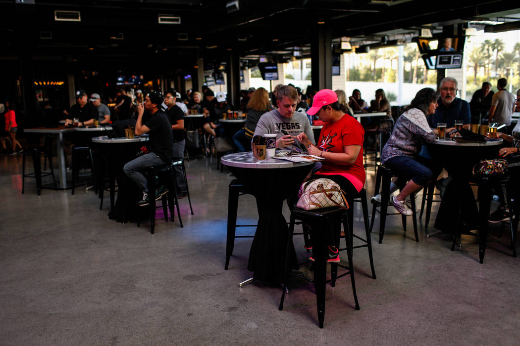 David DeGraw, 36, left and Victoria Sanchez, 31, right, both of Las Vegas sit during a watch party for the Vegas Golden Knights season opener against the Dallas Stars at Topgolf in Las Vegas, Frid ...