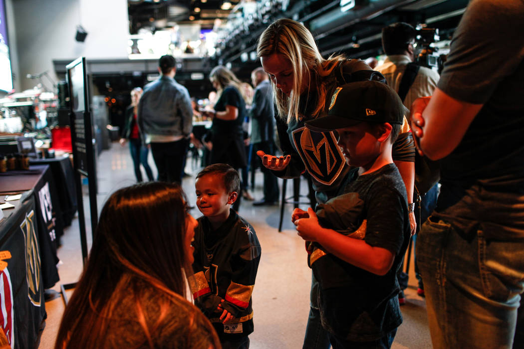 Erika Mox of the Golden Aces, left, speaks with Trysten Tra, 3, second from left, Gabrielle Tra, 33, second from right, and Tyson Tra, 6, right, during a watch party for the Vegas Golden Knights s ...