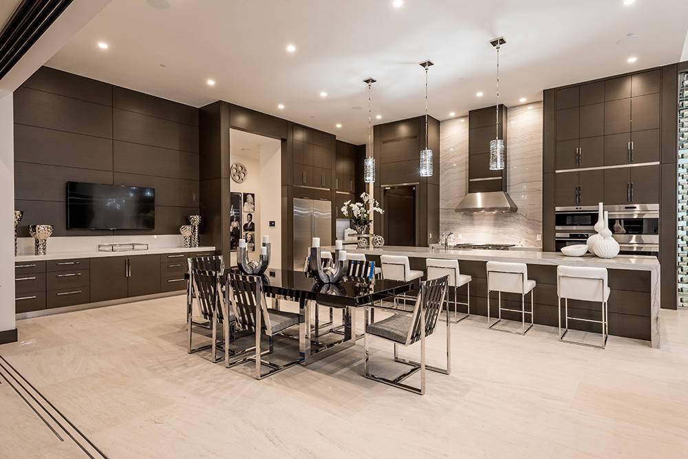 Sun West Custom Homes The gourmet kitchen features oversized limestone floors and a wet bar.