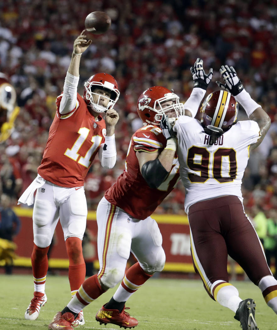 Kansas City Chiefs quarterback Alex Smith (11) throws as offensive lineman Eric Fisher (72) blocks Washington Redskins defensive lineman Ziggy Hood (90) during the second half of an NFL football g ...