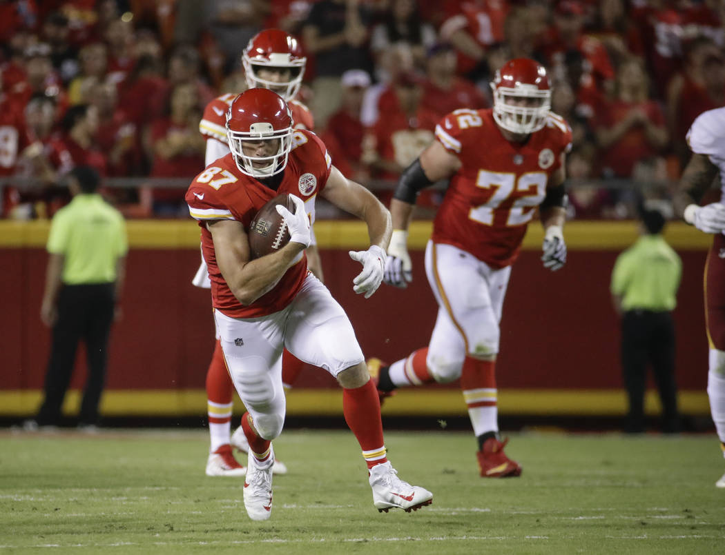 Kansas City Chiefs tight end Travis Kelce (87) carries the ball in front of offensive lineman Eric Fisher (72) and quarterback Alex Smith (11) during the first half of an NFL football game against ...