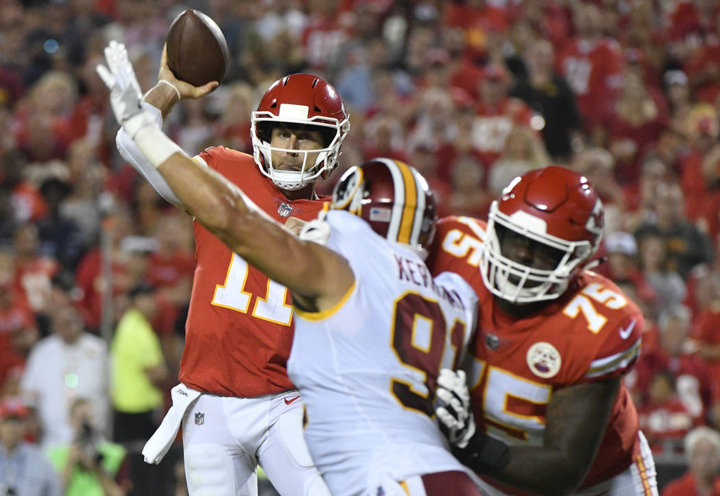 Kansas City Chiefs quarterback Alex Smith (11) throws under pressure from Washington Redskins linebacker Ryan Kerrigan (91) during the second half of an NFL football game in Kansas City, Mo., Mond ...