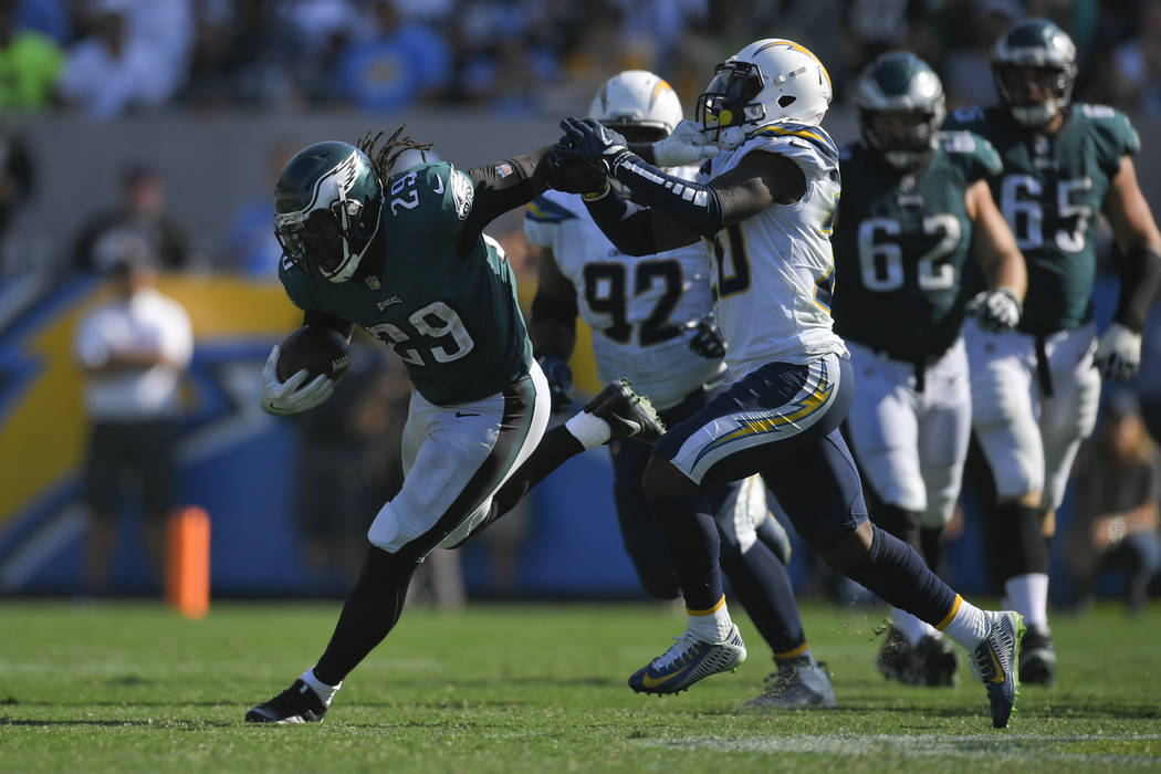 Philadelphia Eagles running back LeGarrette Blount, left, gets a hand on the facemark of Los Angeles Chargers defensive back Desmond King (20) as he runs during the second half of an NFL football  ...