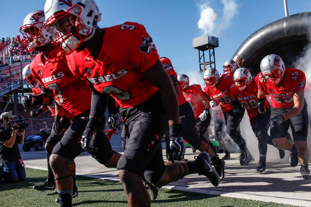 The UNLV Rebels run onto the field before the start of a football game against Utah State Aggies at Sam Boyd Stadium in Las Vegas, Saturday, Oct. 21, 2017. Joel Angel Juarez Las Vegas Review-Journ ...