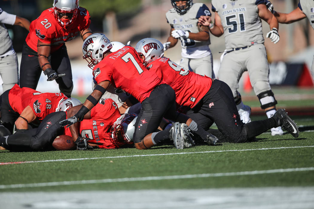 UNLV Rebels linebacker Brian Keyes (5), bottom second from left, recovers a fumble against Utah State Aggies during the first quarter of a football game at Sam Boyd Stadium in Las Vegas, Saturday, ...