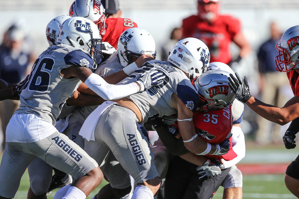 UNLV Rebels running back Xzaviar Campbell (35) is tackled by the Utah State Aggies during the first quarter of a football game at Sam Boyd Stadium in Las Vegas, Saturday, Oct. 21, 2017. Joel Angel ...