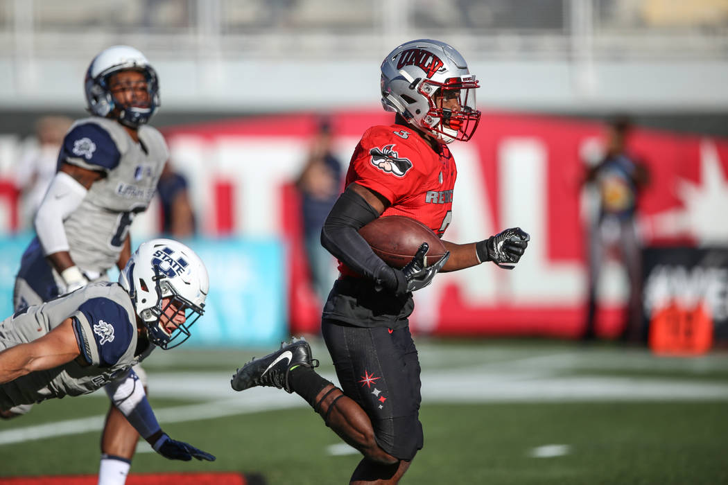 UNLV Rebels running back Lexington Thomas (3), right, runs the ball past the Utah State Aggies for a touchdown during the second quarter of a football game at Sam Boyd Stadium in Las Vegas, Saturd ...