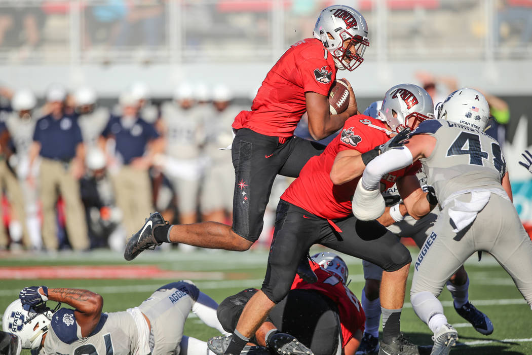UNLV Rebels quarterback Armani Rogers (1), top left, runs the ball for a touchdown against the Utah State Aggies during the second quarter of a football game at Sam Boyd Stadium in Las Vegas, Satu ...