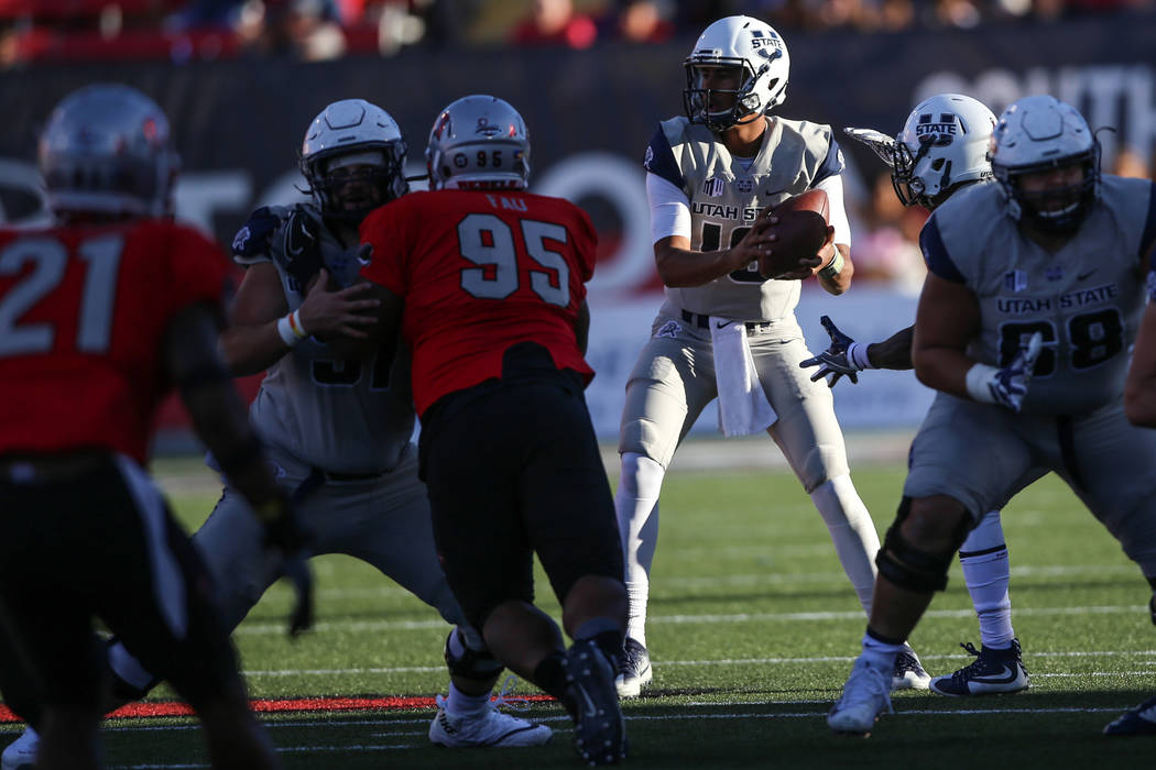 Utah State Aggies quarterback Jordan Love (10), right, prepares to throw a pass against the UNLV Rebels during the second quarter of a football game at Sam Boyd Stadium in Las Vegas, Saturday, Oct ...