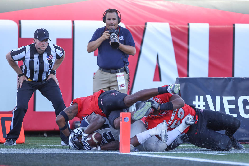 Utah State Aggies running back LaJuan Hunt (21), bottom left, runs the ball against the UNLV Rebels during the second quarter of a football game at Sam Boyd Stadium in Las Vegas, Saturday, Oct. 21 ...