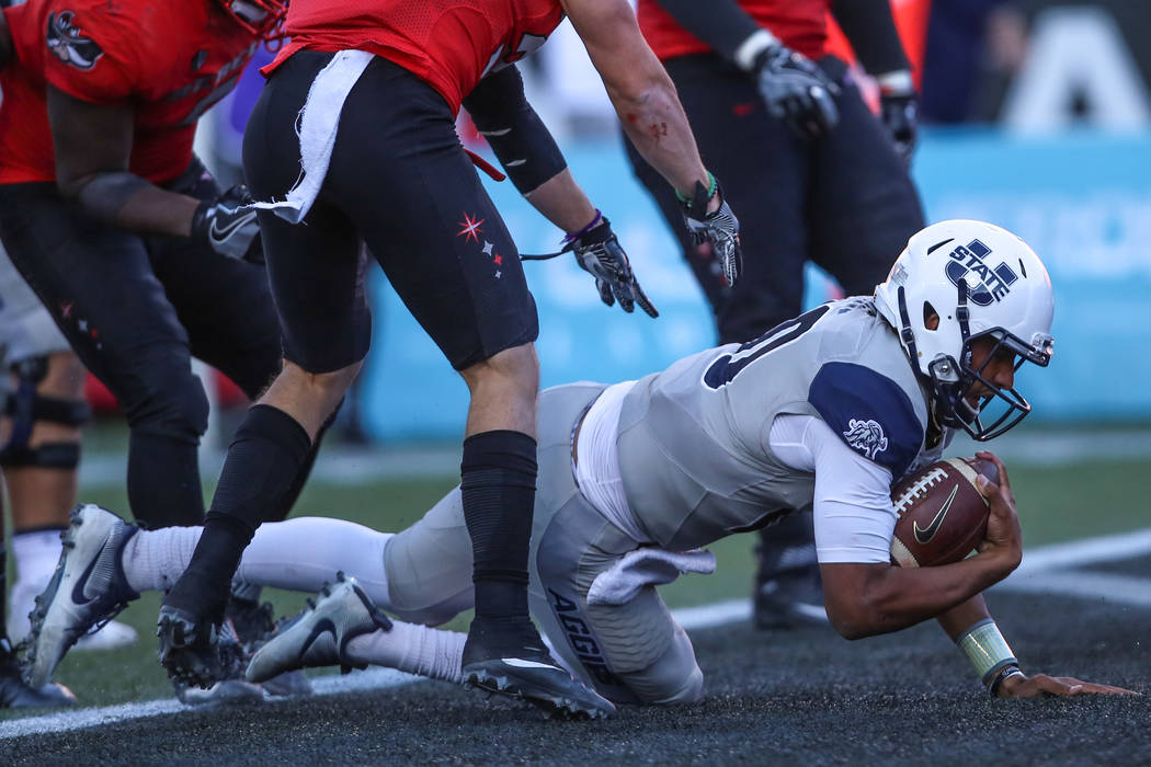 Utah State Aggies quarterback Jordan Love (10), right, scores a touchdown against the UNLV Rebels during the third quarter of a football game at Sam Boyd Stadium in Las Vegas, Saturday, Oct. 21, 2 ...
