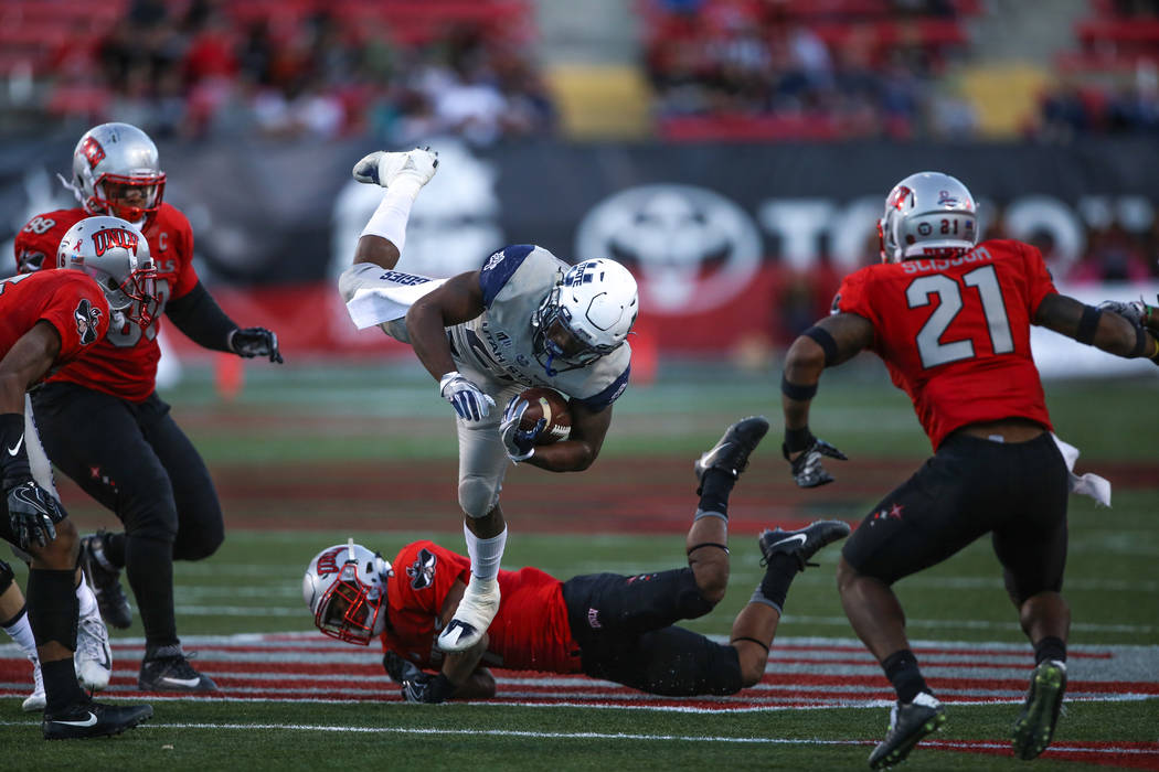 Utah State Aggies running back LaJuan Hunt (21), center, jumps in the air as he falls after running the ball against the UNLV Rebels during the fourth quarter of a football game at Sam Boyd Stadiu ...