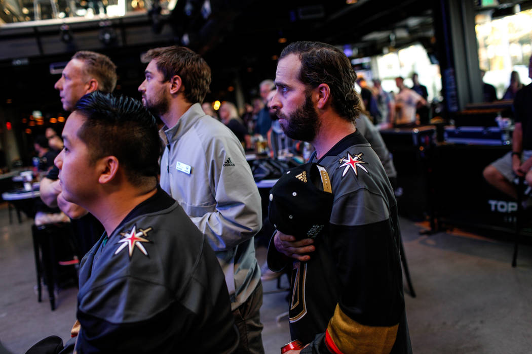 T.J. O'Donnell of Las Vegas, 30, places his hand over his heart during the national anthem at a watch party for the Vegas Golden Knights season opener against the Dallas Stars at Topgolf in Las Ve ...