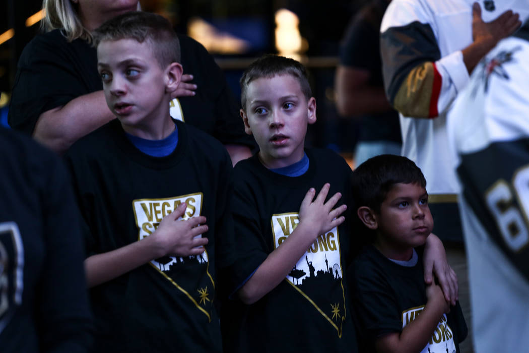 Caleb Damien, 10, left, Bryce Damien, 8, center, and Ruben Del Valle III, 6, right, place their hand over their hearts during the national anthem at a watch party for the Vegas Golden Knights seas ...