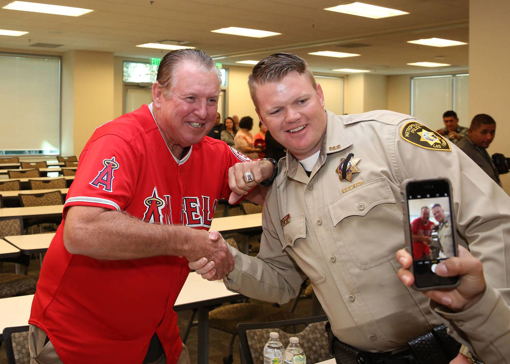 Former Major League Baseball player Mickey Hatcher, left, poses for photo with Las Vegas police officer Reed Dallas at Metropolitan Police Department headquarters on Friday, Oct. 6, 2017, in Las V ...