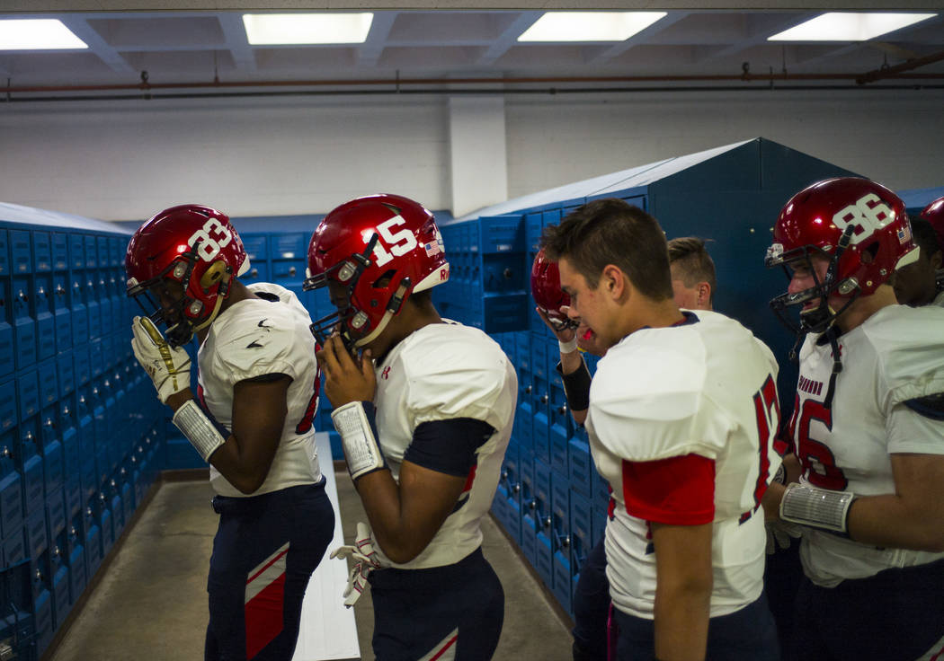 Coronado's Ayzayah Hartfield (15), son of fallen Las Vegas police officer Charleston Hartfield, huddles with teammates for a prayer in the locker room before a football game at Basic High School i ...