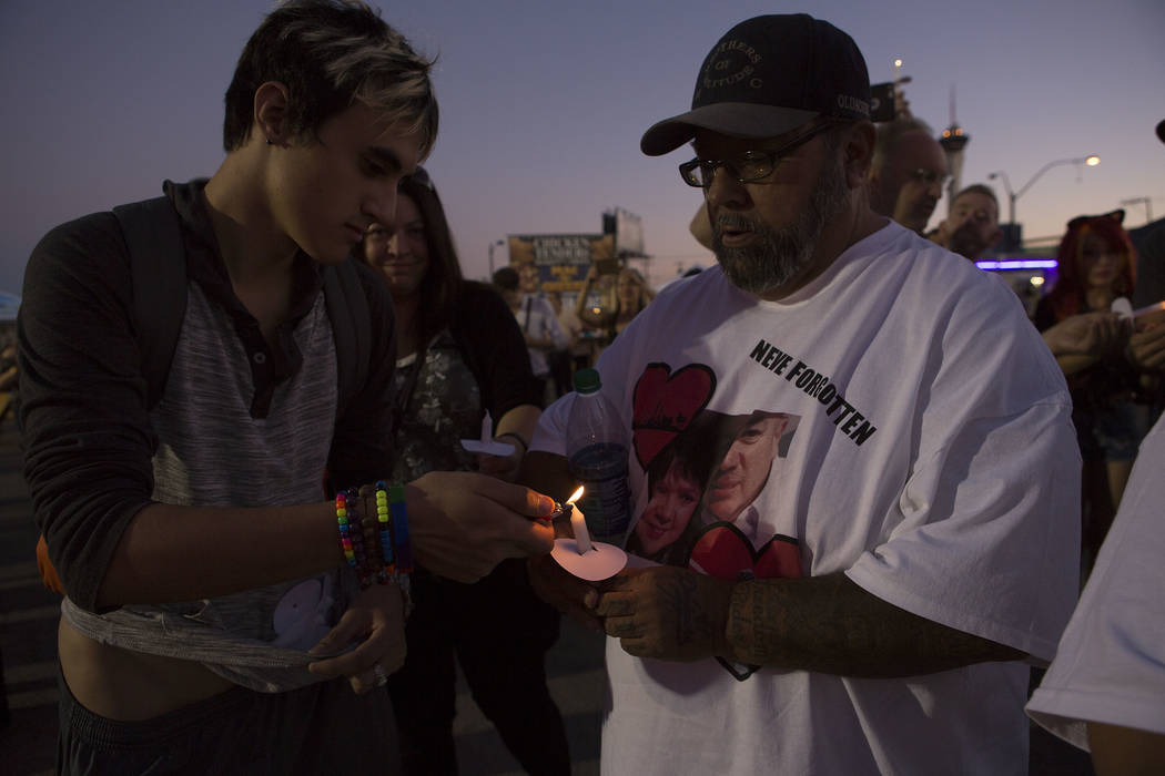 Angel Maiorano, left, helps light Eward Avila's, who lost loved ones in the shooting, candle during First Friday in Las Vegas, Friday, Oct. 6, 2017. This is the 15th anniversary of First Friday do ...
