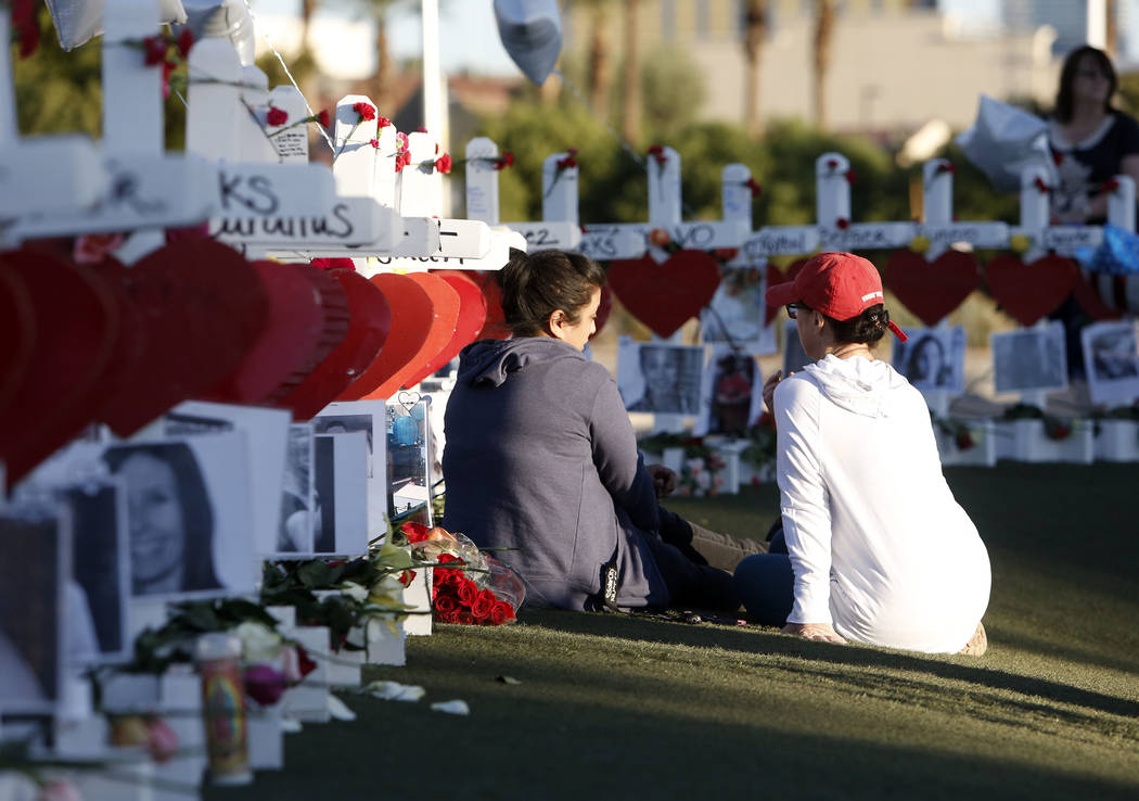 Cece Navarrette, left, and Shelley Boyle share a moment on the Las Vegas Strip where 58 white crosses stand to honor the victims of Sunday's mass shooting on Friday, Oct. 6, 2017, in Las Vegas. Bi ...