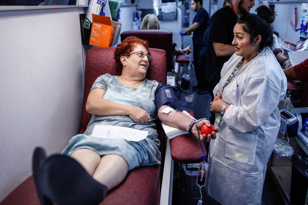 Robyn Stein of Las Vegas, a registered nurse at Southern Hills Hospital, 61, left, donates blood as Blanca Briones of Las Vegas, an assistant donor care supervisor, 43, right, assists her inside a ...