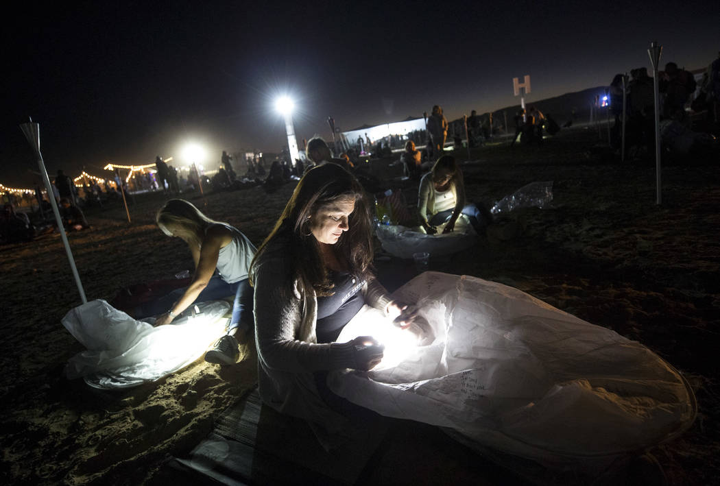 Terri Alzado of Florida writes a message on a lantern during the RiSE Lantern Festival held at the Moapa River Indian Reservation on Friday, Oct. 6, 2017. Richard Brian Las Vegas Review-Journal @v ...