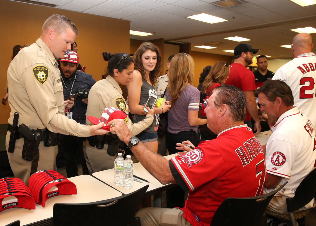 Former Major League Baseball players Mickey Hatcher, left, and Chuck Finley sign autographs for Las Vegas Metro Police officers Reed Dallas, left, and Sgt. Mitchell Tavarez at LVMPD Headquarters o ...