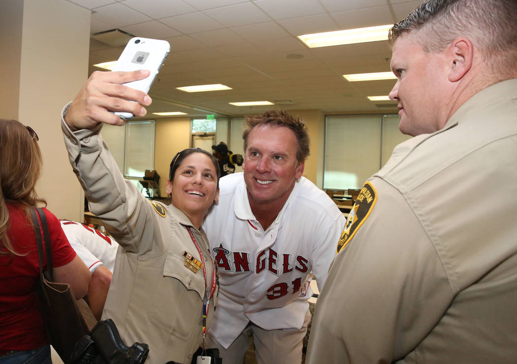 Sgt. Mitchell Tavarez of the Las Vegas Metro Police Department, takes a selfie with former Major League Baseball player Chuck Finley as officer Reed Dallas, right, looks on at LVMPD Headquarters o ...