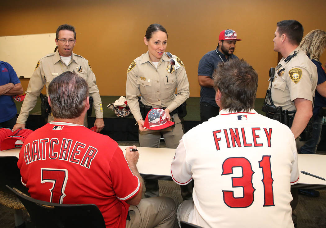 Former Major League Baseball players Mickey Hatcher, left, and Chuck Finley sign autographs for Las Vegas Metro Police officers Richard Tusko, left, and Maribel Suey, center, at LVMPD Headquarters ...