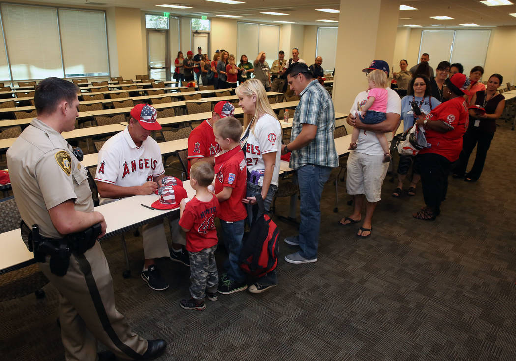 Former Major League Baseball players Mickey Hatcher, left, and Chuck Finley sign autographs for family members of the Las Vegas Metro Police Departmen at LVMPD Headquarters on Friday, Oct. 6, 2017 ...