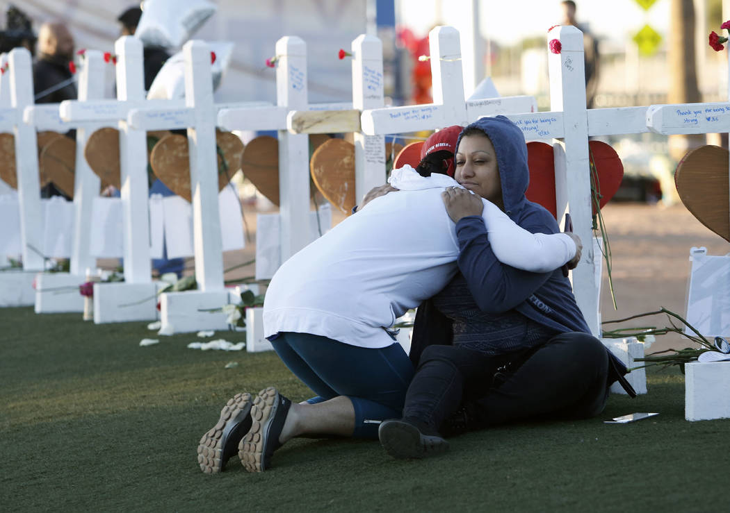 Shelley Boyle, left, and Cece Navarrette comfort each other on the Las Vegas Strip where fifty-eight white crosses stand to honor the victims of Sunday's mass shooting on Friday, Oct. 6, 2017, in  ...