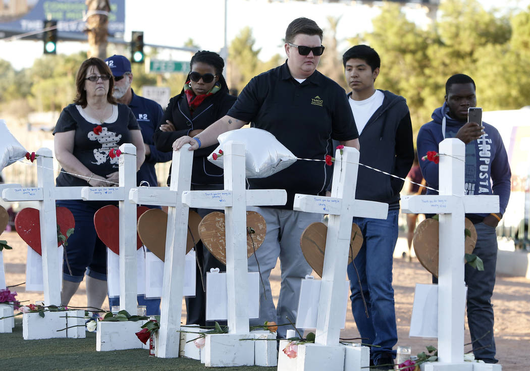 People gather on the Las Vegas Strip where fifty-eight white crosses stand to honor the victims of Sunday's mass shooting on Friday, Oct. 6, 2017, in Las Vegas. Bizuayehu Tesfaye Las Vegas Review- ...