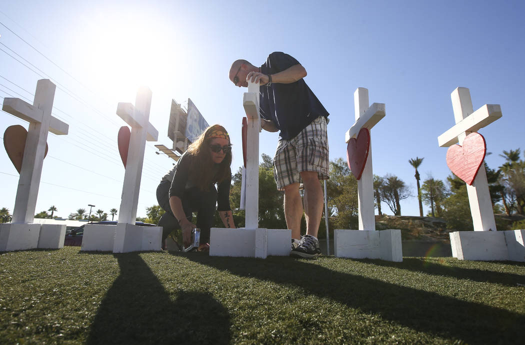 """Sherri Camperchioli, left, and Jordan Cassel place photos of victims of Sunday's mass shooting on crosses left in their memory near the """"Welcome to Fabulous Las Vegas"""" sign in La ..."""