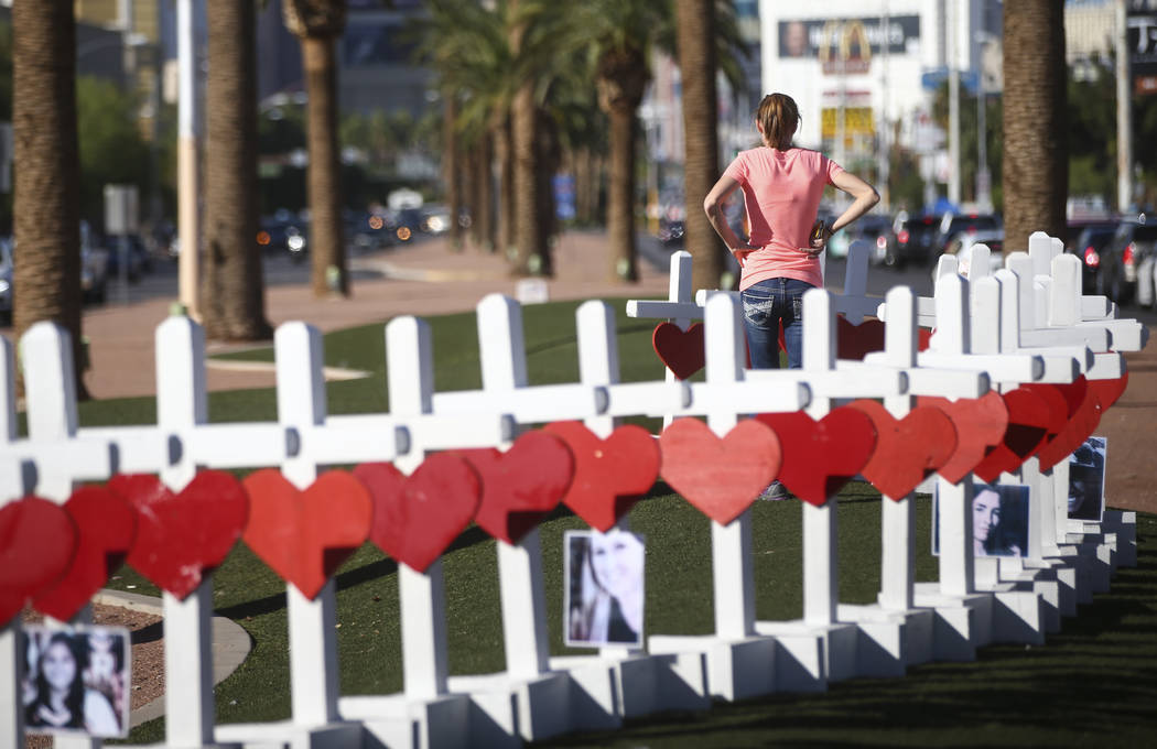 """People look at crosses for the victims of Sunday's mass shooting placed near the """"Welcome to Fabulous Las Vegas"""" sign in Las Vegas on Thursday, Oct. 5, 2017. Chase Stevens Las Ve ..."""