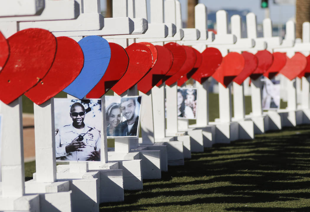 """Photos of victims of Sunday's mass shooting on crosses left in their memory near the """"Welcome to Fabulous Las Vegas"""" sign in Las Vegas on Thursday, Oct. 5, 2017. Chase Stevens La ..."""