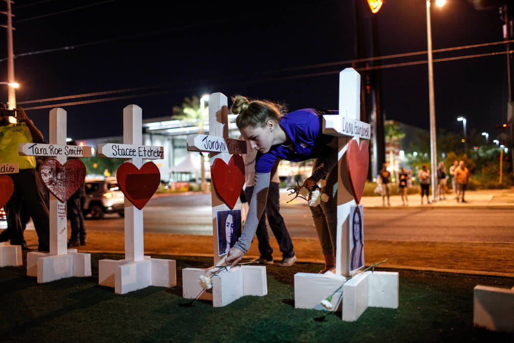 Victoria Karp of Las Vegas and student at Bishop Gorman, 17, places flowers at crosses honoring the victims of Sunday night's shooting during a vigil at the Welcome to Fabulous Las Vegas sign in L ...