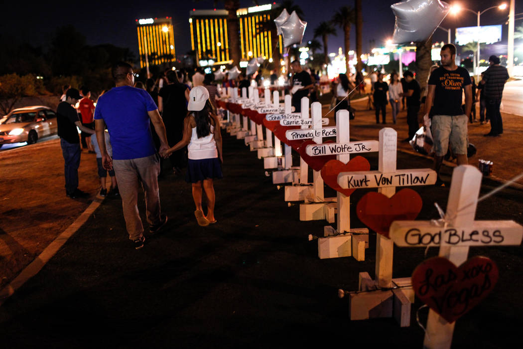 Humberto Solano of Las Vegas, 44, and his daughter Delayla, 7, hold hands as they walk past crosses honoring the victims of Sunday night's shooting during a vigil at the Welcome to Fabulous Las Ve ...