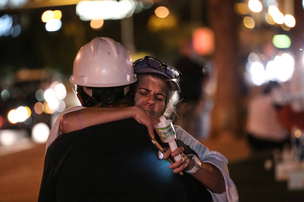 Greg Zanis is hugged by Lee Pex during a vigil in remembrance of the victims of Sunday night's shooting at the Welcome to Fabulous Las Vegas sign in Las Vegas, Thursday, Oct. 5, 2017. Joel Angel J ...