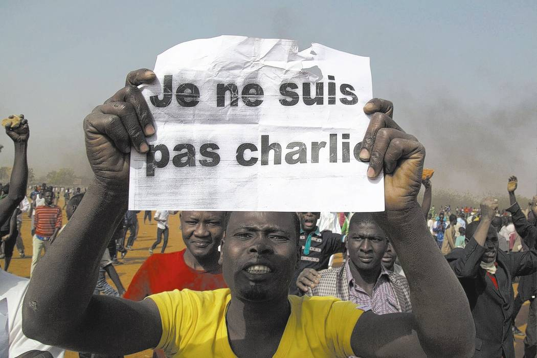 A man holds a sign during a protest against Niger President Mahamadou Issoufou's attendance last week.
