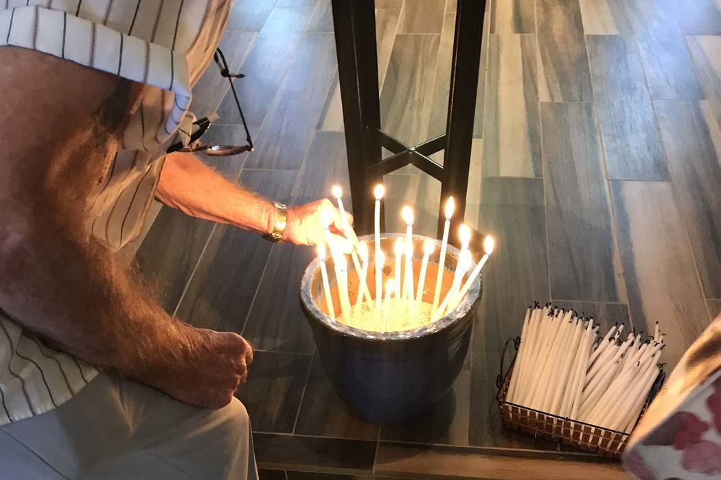 A congregant lights a candle on Sunday, Oct. 8, 2017, at Reformation Lutheran Church in Las Vegas in honor of the victims of the Oct. 1 mass shooting on the Las Vegas Strip. (Betsy Helfand/Las Veg ...