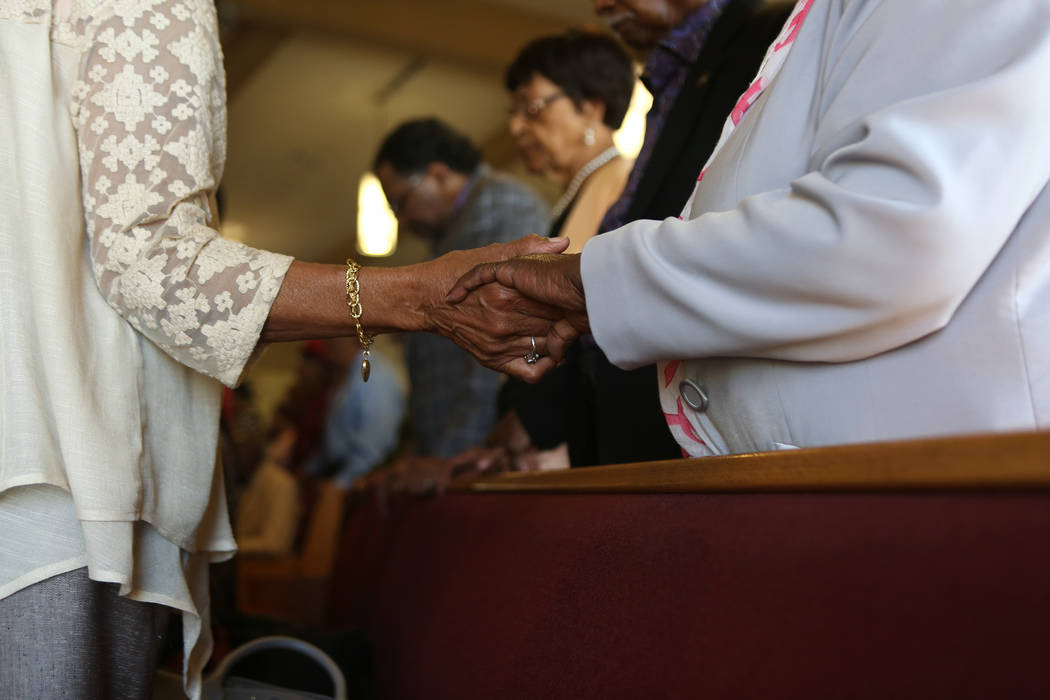 Church attendees link hands while the fallen Route 91 Harvest festival victims' names are read during a First African-Methodist Episcopal Church service in North Las Vegas, Sunday, Oct. 8, 2017. E ...