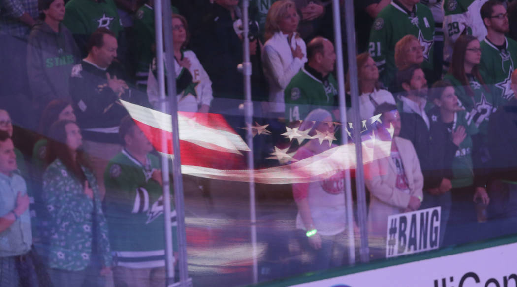 Fans stand during the national anthem before an NHL hockey game between the Vegas Golden Knights and Dallas Stars in Dallas, Friday, Oct. 6, 2017. (AP Photo/LM Otero)