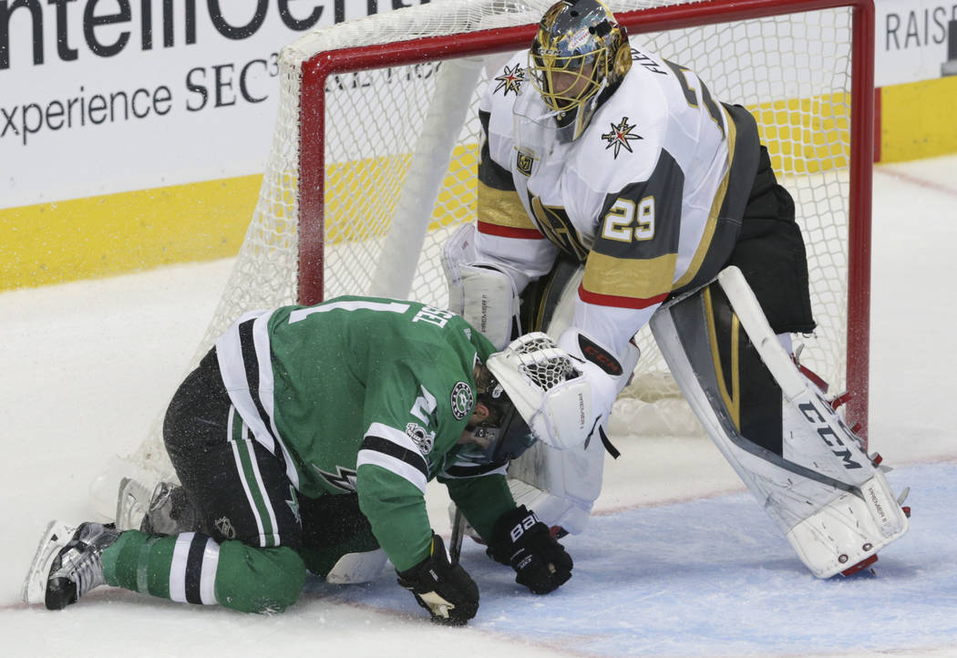 Vegas Golden Knights goalie Marc-Andre Fleury (29) pushes Dallas Stars left wing Antoine Roussel (21) out of the crease during the first period of an NHL hockey game in Dallas, Friday, Oct. 6, 201 ...