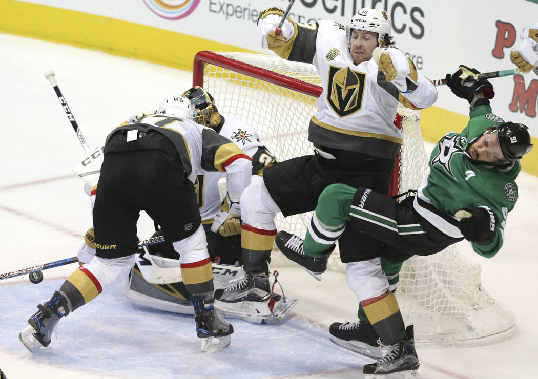 Dallas Stars center Tyler Seguin (91) is hit by Vegas Golden Knights James Neal (18) as teammates Luca Sbisa (47) and goalie Marc-Andre Fleury cover the goal during the second period of an NHL hoc ...