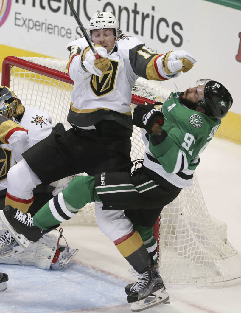 Vegas Golden Knights' James Neal (18) hits Dallas Stars center Tyler Seguin (91) in front of the goal during the second period of an NHL hockey game in Dallas, Friday, Oct. 6, 2017. The Golden Kni ...