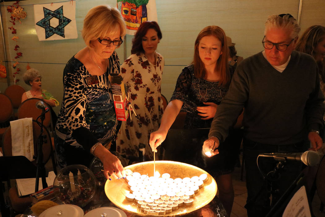 Roberta Unger, from left, Jessica Hutchings. Sara Ross, and her father Donald Ross light the candles for the victims of the Las Vegas shooting at Congregation Ner Tamid in Henderson, Friday, Oct.  ...