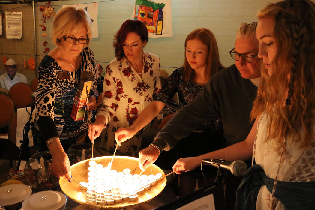 Roberta Unger, from left, Jessica Hutchings, Sara Ross, her father Donald Ross and her sister Samantha Ross light the candles for the victims of the Las Vegas shooting at Congregation Ner Tamid in ...